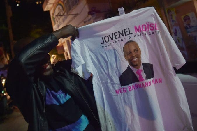 A supporter celebrates the victory of Jovenel Moise following preliminary results in the first round of Haiti's presidential election on November 28, 2016 in the commune of Petion Ville, in the Haitian capital Port-au-Prince. Haitian businessman Jovenel Moise, the candidate backed by former president Michel Martelly, won the presidential vote in the first round, official early results showed,  ahead of Jude Celestin, candidate of the opposition LAPEH, scoring 55.67 percent against 19.52 percent.   / AFP / HECTOR RETAMAL