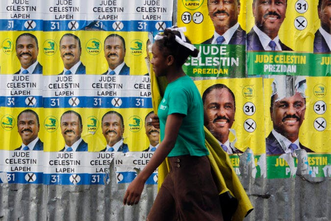 A woman walks past a metal sheeting covered with campaign posters promoting presidential candidate Jude Celestin, in Port-au-Prince, Haiti, Friday, Nov. 18, 2016. Haitians are going to the polls Sunday to pick Haiti's next president. Haiti is holding long-delayed presidential elections Sunday. Last year's vote was annulled and the nation has been operating with a provisional president since February. (AP Photo/Ricardo Arduengo)