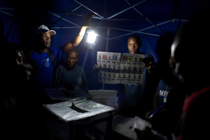Electoral workers count election ballots by Lamp light, due to the electricity not working at the polling station, during elections in Port-au-Prince, Haiti, Sunday, Nov. 20, 2016. Haiti's repeatedly derailed presidential election got underway more than a year after an initial vote was annulled. ( AP Photo/Dieu Nalio Chery)