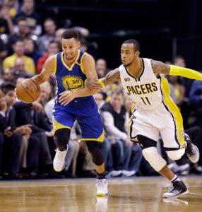 Stephen Curry (izquierda) de los Warriors de Golden State se desprende con el balón ante Monta Ellis de los Pacers de Indiana, el lunes 21 de noviembre de 2016. (AP Foto/Darron Cummings)