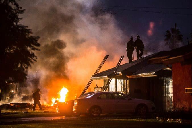 Una columna de humo y fuego marca el lugar en el que un pequeño avión se estrelló sobre dos viviendas en Riverside, en el sur de California, el 27 de febrero de 2017. Cuatro personas murieron y otras dos resultaron heridas en el siniestro. (Watchara Phomicinda/The Press-Enterprise via AP)