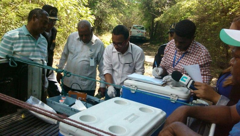Técnicos de Medio Ambiente hacen anotaciones tras tomar muestras del agua para examinarla.