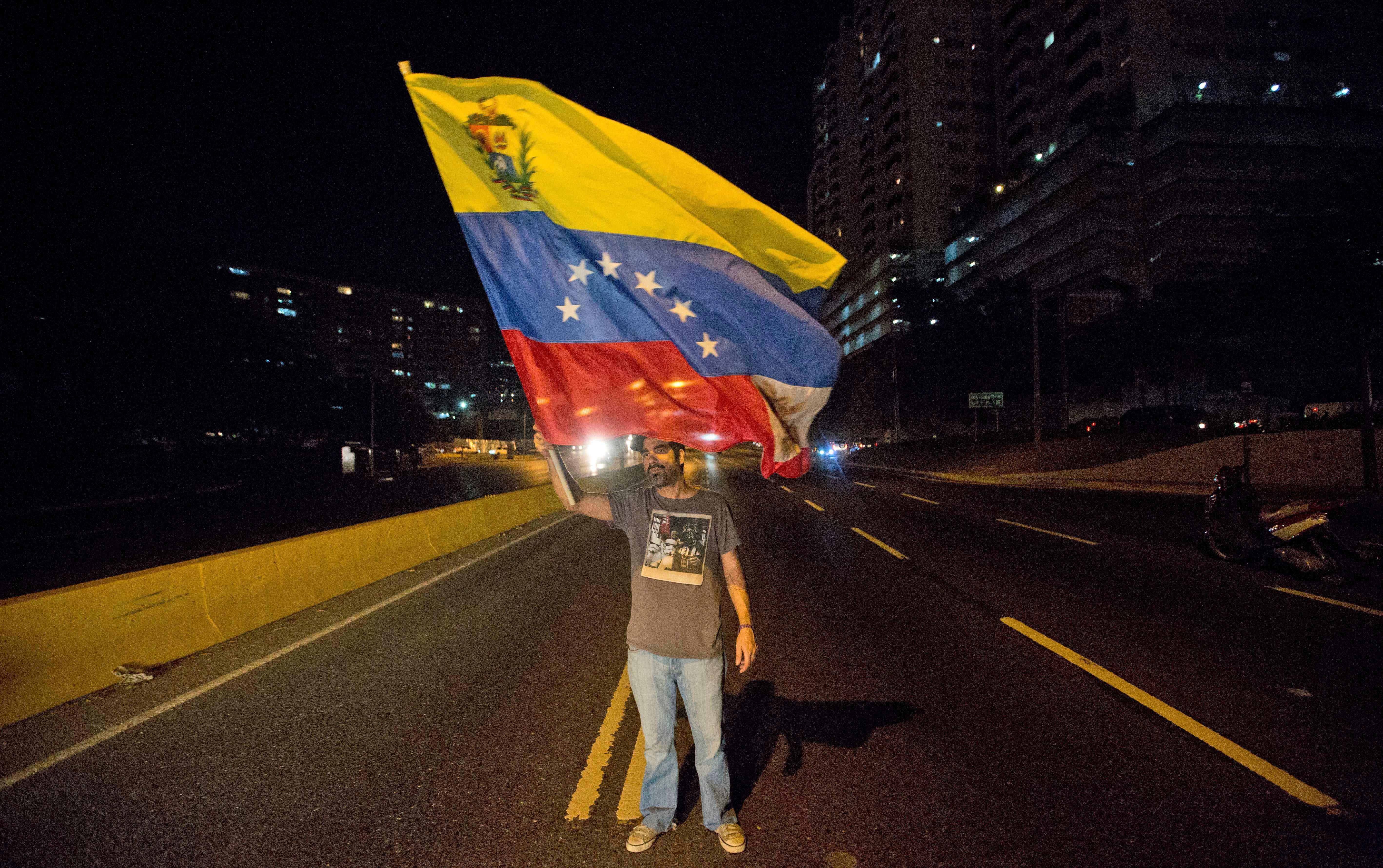 Un dirigente opositor agita una bandera venezolana durante una protesta contra el presidente Nicolás Maduro en Caracas, Venezuela