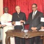 Modesto Guzmán  sostiene junto a Nicolás de Jesús Cardenal López Rodríguez  y Jude Thaddeus Okolo, un sobre de primer día con la emisión postal alusiva a los Papas Benedicto XVI y Francisco/Foto: Fuente externa.