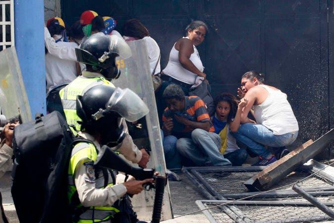 """Manifestantes contrarios al gobierno de Venezuelas se ponen a cubierto ante el avance de agentes de la Policía Bolivariana durante protestas en Caracas, Venezuela, el 19 de abril de 2017. Decenas de miles de opositores al presidente Nicolás Maduro inundaron las calles de Caracas para la calificada como la """"madre de todas las marchas"""" contra el cuestionado mandatario. (AP Foto/Fernando Llano)"""