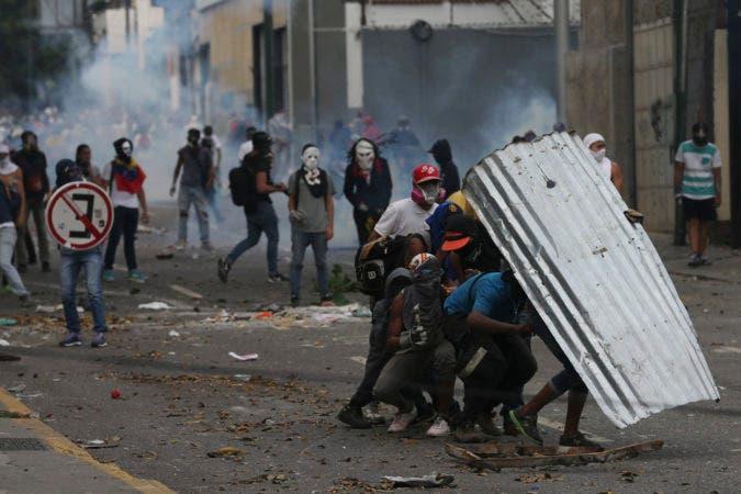 Manifestantes se cubren con un metal corrugado durante las protestas. Fuente externa.
