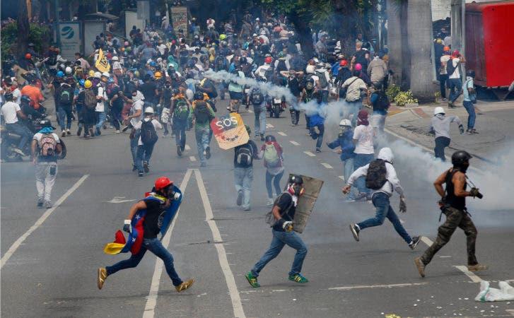 Manifestantes antigubernamentales se enfrentan con fuerzas de seguridad que les impiden el paso con gases lacrimógenos para que no lleguen al Consejo Nacional Electoral en Caracas, Venezuela, el miércoles 24 de mayo de 2017. (AP Foto/Ariana Cubillos)