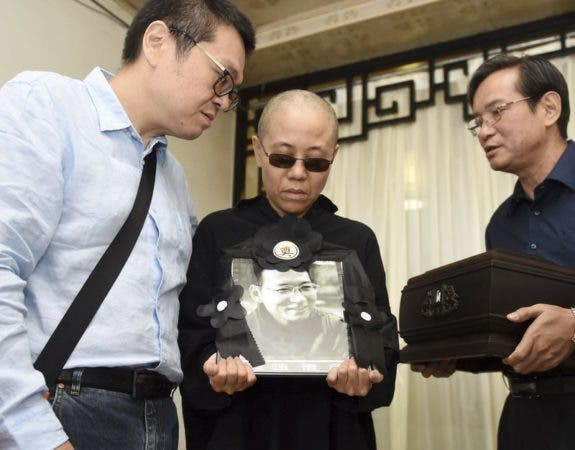 En esta imagen, proporcionada por la Oficina de Información Municipal de Shenyang, Liu Xia (centro), la esposa del fallecido disidente y Premio Nobel de la Paz Liu Xiaobo, sostiene un retrato suyo durante su funeral, en una funeraria en Shenyang, en el noreste de la provincia china de Liaoning, el 15 de julio de 2017. En la imagen aparecen, de izquierda a derecha, Liu Hui, hermano menor de Liu Xia; Liu Xia y Liu Xiaoxuan, hermano pequeño de Liu Xiaobo, quien sostiene las cenizas del fallecido. (Oficina de Información Municipal de Shenyang via AP)