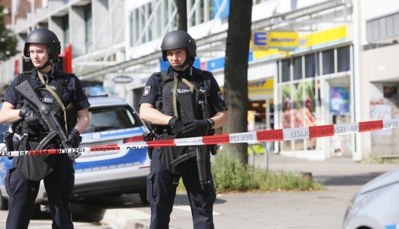 Dos policías custodian la zona acordonada alrededor del supermercado de Hamburgo donde se ha registrado un ataque este viernes. PAUL WEIDENBAUM. (AP).