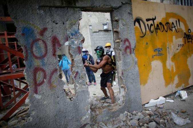 En esta imagen del viernes 4 de agosto de 2017, un manifestante en contra del gobierno, con el rostro cubierto con una máscara, derriba una pared para obtener pedazos de concreto para arrojar a la Policía Nacional Bolivariana durante una protesta en contra de la instalación de una Asamblea Constituyente en Caracas, Venezuela. Es casi un hecho que la instalación de la Asamblea Constituyente intensificará la crisis política que ha generado cuatro meses de manifestaciones, durante las cuales han muerto al menos 120 personas, y cientos más han sido encarceladas