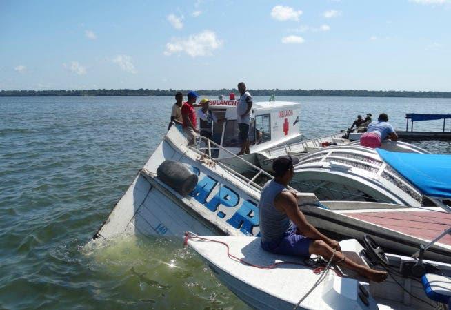"""Personas rodean la embarcación """"Comandante Ribeiro"""" que se hundió mientras llevaba a 70 personas durante una misión de búsqueda y rescate en el Río Xingu, del estado de Pará, en Brasil, el miércoles 23 de agosto de 2017. La oficina de seguridad pública del estado de Pará dijo que 15 personas lograron llegar a la orilla y se recuperaron 10 cuerpos, mientras que el resto permanecen desaparecidos. Las autoridades señalan que la embarcación viajaba en el Río Xingu al momento del naufragio la tarde del martes. Se desconoce de momento la causa del hundimiento. (Alexandre Cardoso via AP)."""