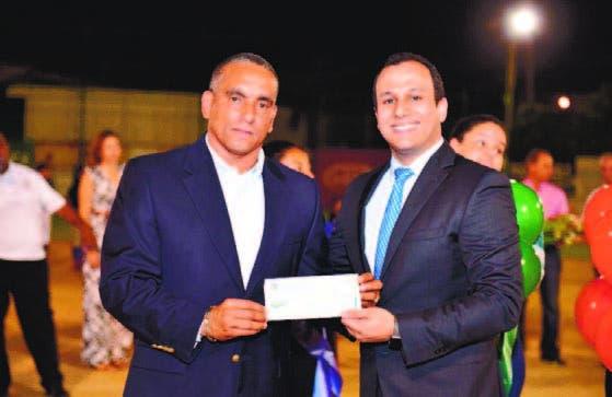 Michael Matos, entrega el aporte de la Presidencia a Alfredo Basset.