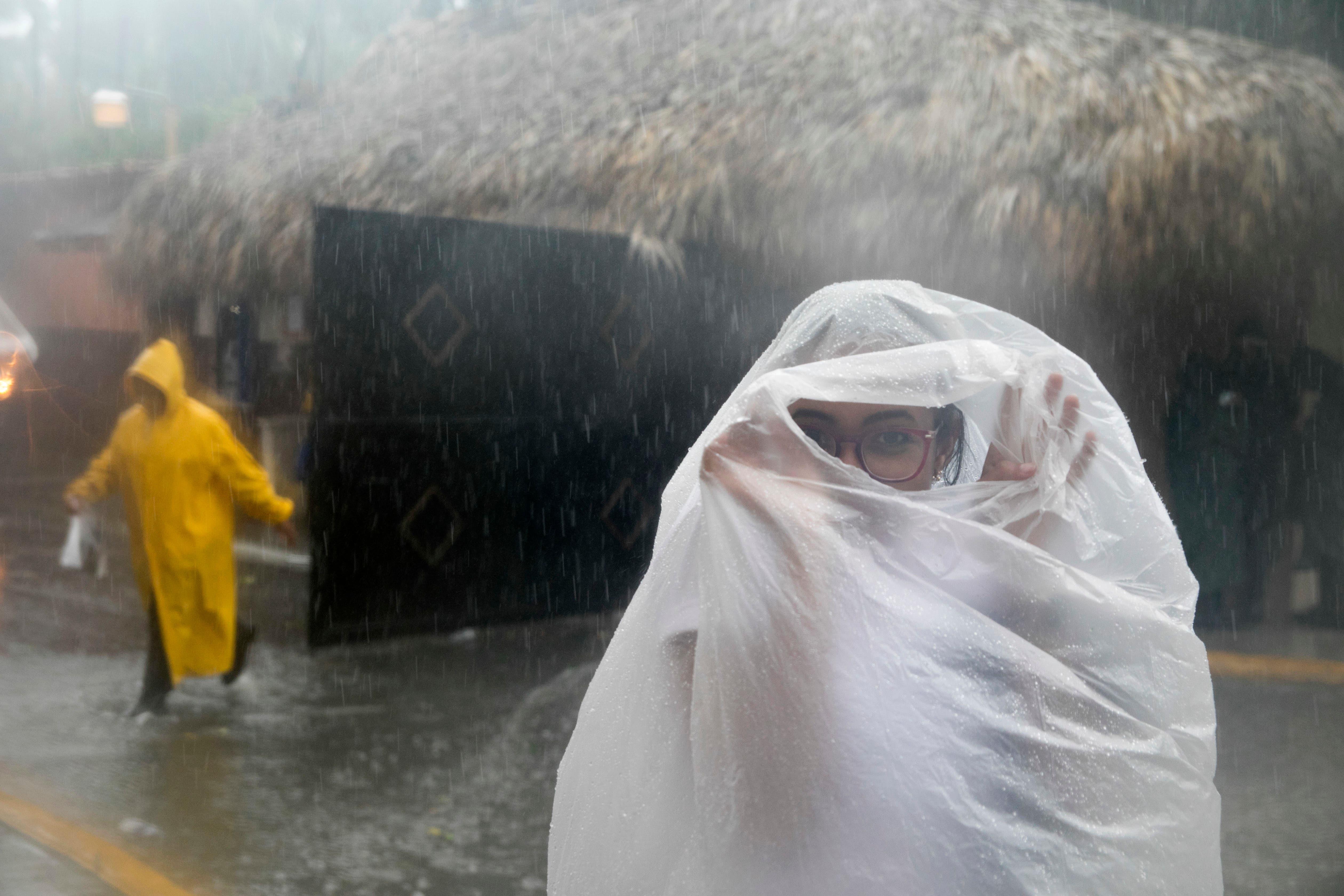 Una mujer se cubre con una bolsa de plástico mientras se dirige a su trabajo en momentos en que el huracán Maria se acerca a la costa de Bavaro, República Dominicana.