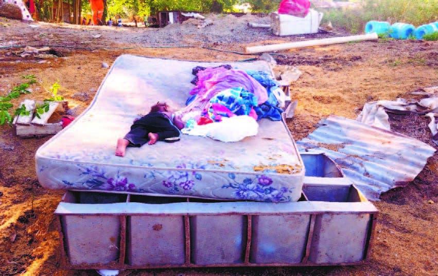 Una pequeña niña descansa sobre un colchón húmedo que recuperaron río abajo. Lo perdieron todo.