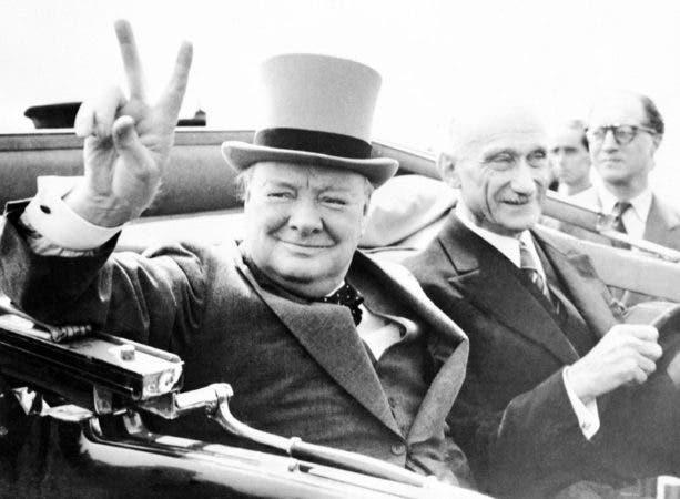 """El ex primer ministro británico Winston Churchill hace su famosa señal de la V desde un auto en Metz, Francia, durante las celebraciones del Día de la Toma de la Bastilla. Churchill fue un prolífico escritor cuyo cuerpo de trabajo incluyó una historia sobre la Segunda Guerra Mundial, el conflicto con el que ha sido más asociado. Cuando ganó el Premio Nobel de Literatura en 1953, fue elogiado """"por su maestría para descripciones históricas y biográficas así como su brillante oratoria al defender valores humanos elevados""""."""