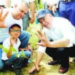 El ministro Francisco Domínguez junto a un niño planta un árbol