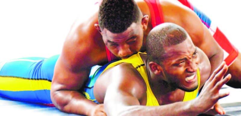 El luchador dominicano José Arias somete a la obediencia a su rival de Venezuela, combate en que logró ganar la primera medalla de oro para el país en los Jueg os