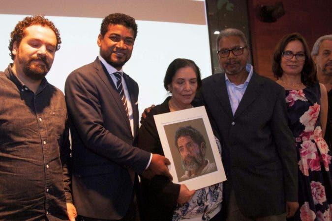 Los hijos del extinto artista plástico, Domingo Liz,  Mercedes Morales y Pablo Liz, respectivamente, reciben  un dibujo trabajado por Gabino Ortiz, como reconocimiento al aporte que su padre realizara las  artes plásticas del país.