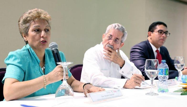 La doctora Rosario Espinal durante la presentación, escucha Rafael Toribio y Roberto Obando Prestol.