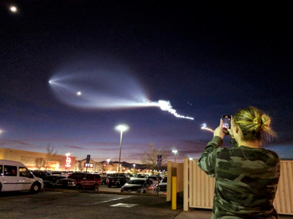A Hair Salon worker photographs the light display of SpaceX's Falcon 9 rocket launch, Friday, Dec. 22 2017, in Apple Valley, Calif. The launch was more than 200 miles from Apple Valley yet was still brilliantly visible. The Falcon 9 booster lifted off from coastal Vandenberg Air Force Base, carrying the latest batch of satellites for Iridium Communications. (James Quigg/The Daily Press via AP)