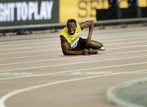 El velocista jamaiquino Usain Bolt aparece tirado en el suelo tras lesionarse en la final de los 4x100 metros en el Mundial de Atletismo en Londres.
