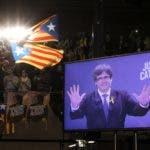 Gente ondeando banderas catalanas mientras el depuesto expresidente regional de Cataluña Carles Puigdemont aparece en una pantalla en una retransmisión en vivo desde Bruselas, durante un acto de campaña para las elecciones regionales de Cataluña, en Barcelona, España. (AP Foto/Emilio Morenatti)
