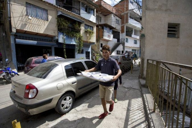 un voluntario lleva una bandeja de comida para servir a los vecinos en un comedor social impulsado por la oposición en Caracas, Venezuela. (AP Foto/Fernando Llano).