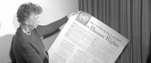 La Señora Eleanor Roosevelt de los Estados Unidos, presidenta del comité de redacción, sostiene la Declaración Universal de los Derechos Humanos en inglés. Foto ONU (1949).