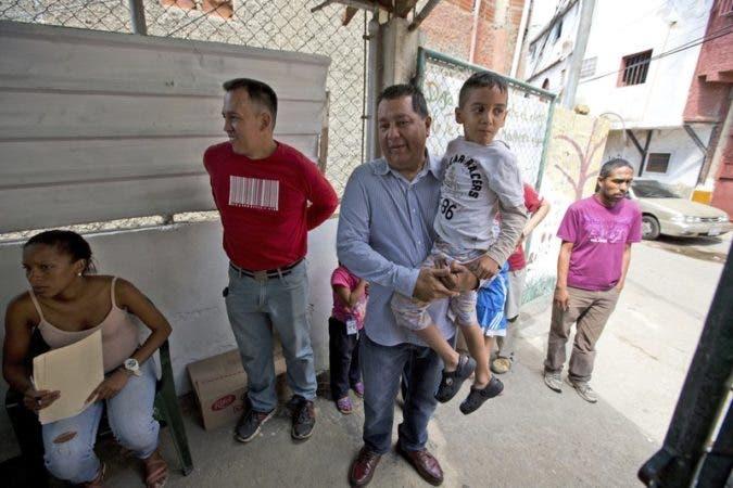 El político opositor Miguel Castillo sostiene a un chico discapacitado de seis años llamado Tomás ante un comedor social impulsado por la oposición, donde el pequeño puede tomar una comida gratis, en Caracas, Venezuela. (AP Foto/Fernando Llano).