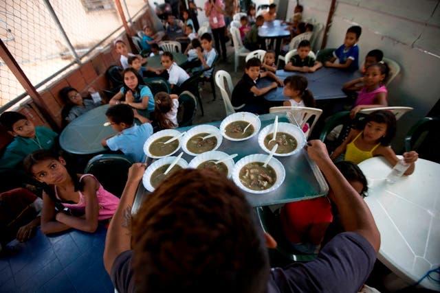 En esta imagen del 12 de diciembre de 2017, niños esperando a que les sirvan una comida gratis en un comedor social impulsado por la oposición en Caracas, Venezuela. Líderes de la oposición venezolana se están reinventando, reuniéndose con el creciente número de pobres en sus propios barrios. (AP Foto/Fernando Llano)