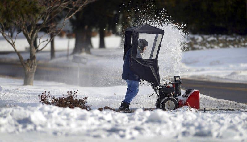 Un residente limpia  la nieve de la entrada a una casa en Church Street, Moscow, Pennsylvania, el 5 de enero de 2018. (Butch Comegys/The Times & Tribune via AP)