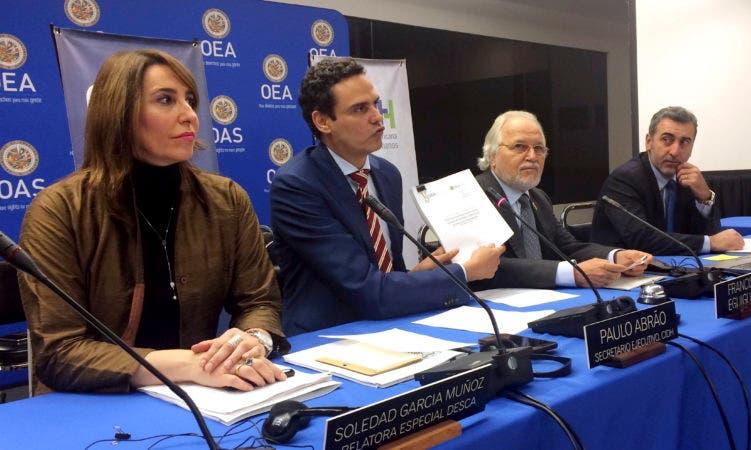 El secretario general de la Comisión Interamericana de Derechos Humanos, Paulo Abrão, segundo desde la izquierda, muestra una copia de un reporte sobre derechos humanos en Venezuela, en Washington, el lunes 12 de febrero de 2018. (AP Foto/Luis Alonso Lugo)