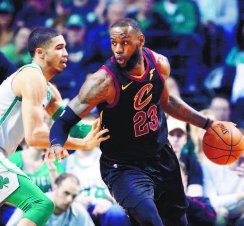 LeBron James (23), de Cleveland, conduce el balón ante Jayson Tatum, de Boston, en el choque de ayer.