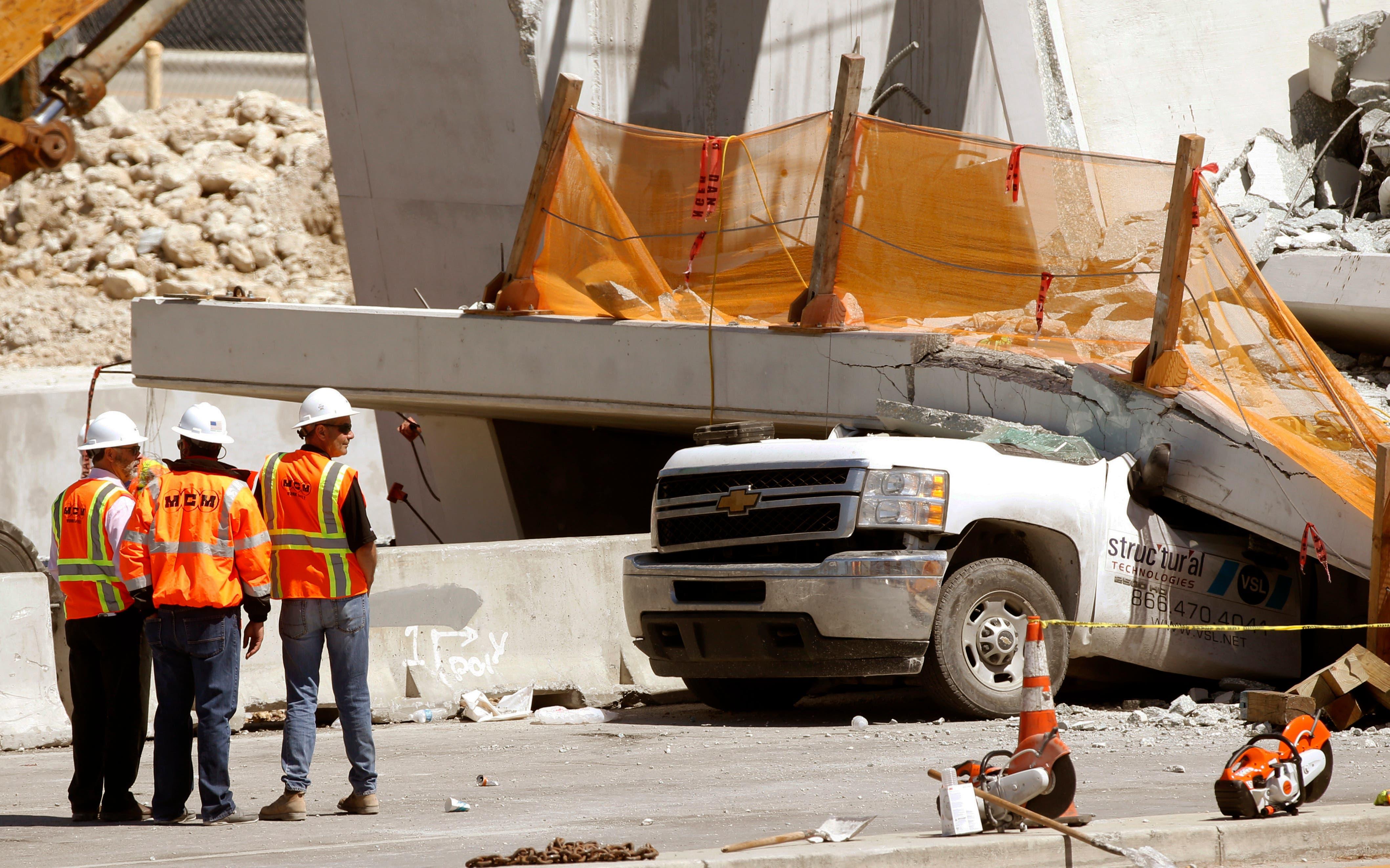 Varios trabajadores de pie el viernes 16 de marzo de 2018 junto a una sección de un puente peatonal colapsado un día antes cerca de la Universidad Internacional de Florida en la zona de Miami. (AP Foto/Wilfredo Lee)