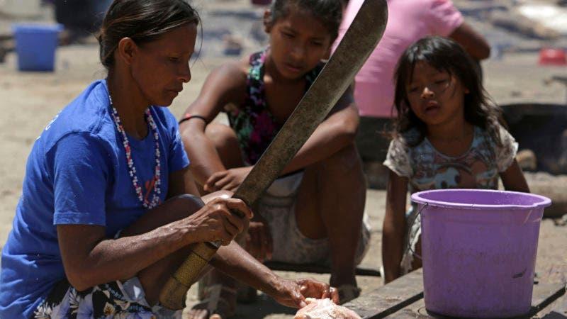En esta imagen, tomada el 10 de marzo de 2018, una mujer de la comunidad indígena venezolana warao corta un pollo para cocinar en la cocina al aire libre de un albergue en Pacaraima, el principal punto de llegada de venezolanos al estado brasileño de Roraima. Muchos de los warao entrevistados dijeron que el gobierno socialista de Venezuela encabezado por el presidente Nicolás Maduro los abandonó hasta el punto de que en las zonas en las que vivían no había servicios ni comida. (AP Foto/Eraldo Peres)