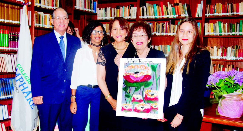 La escritora Jeannette Miller recibe un obsequio de los estudiantes acompañada por la directora del colegio, Maritza Florentino, y José