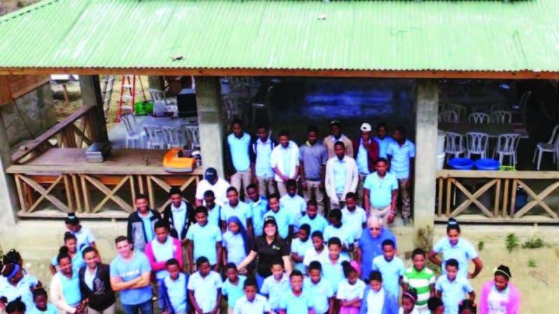 Niños de la escuela San José de Joca en Pedro Santana junto a los voluntarios de Nature Power luego de instalar los paneles solares.