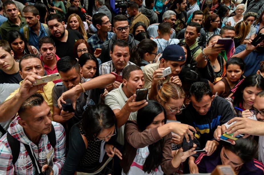 Venezolanos toman fotos a los requisitos dispuesto por las autoridades para salir del país.