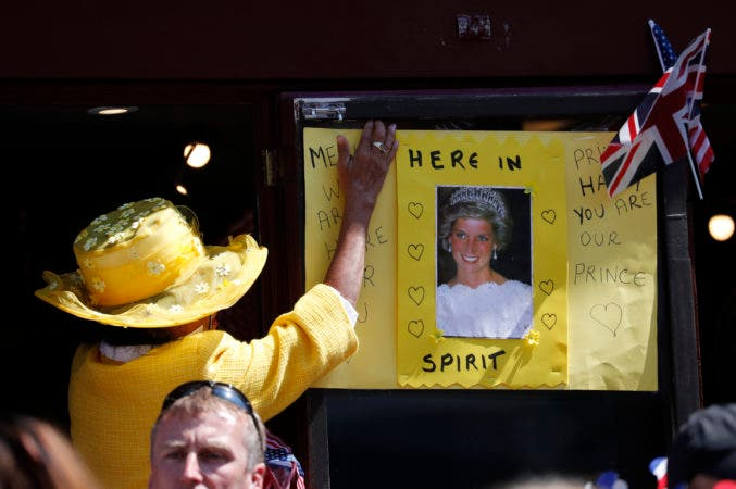30. Una mujer coloca un póster con una foto de la princesa Diana fuera de la ceremonia nupcial del príncipe Harry y Meghan Markle en la capilla de San Jorge