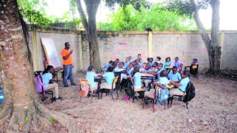 Los niños de la escuela Básica Manuel Llanes reciben clase bajo varios árbole s.