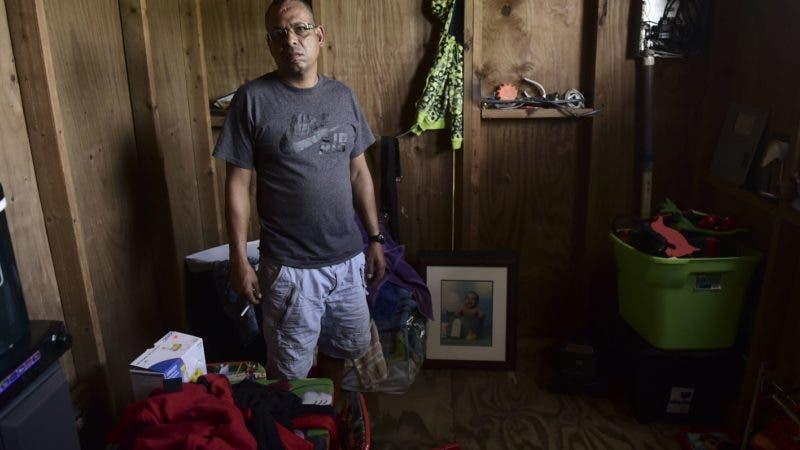 En esta imagen del 13 de junio de 2018, Gabriel Figueroa posa para una foto dentro de una de las habitaciones en la casa que tiene arrendada, que sufrió daños al paso del huracán María, en la  Barriada Figueroa de San Juan, Puerto Rico. (AP Foto/Carlos Giusti)