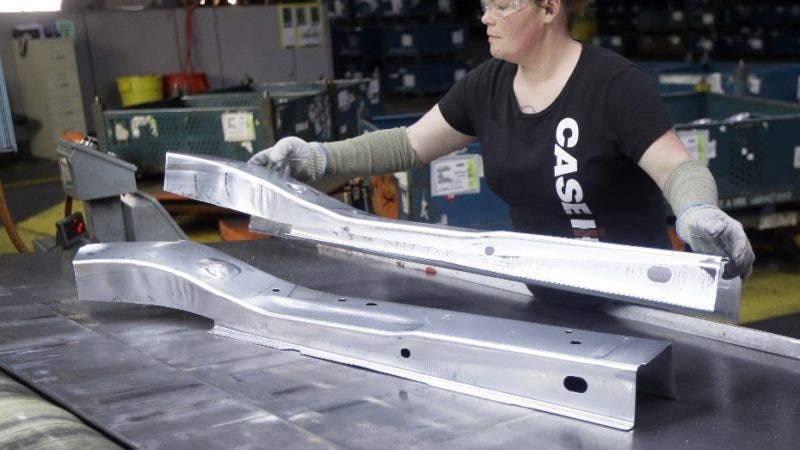 FILE- In this April 30, 2015, file photo, United Auto Workers line worker Crystal McIntyre unloads parts from a stamping machine at the General Motors Pontiac Metal Center in Pontiac, Mich. If President Donald Trump delivers on threats to slap 25 percent tariffs on imported automobiles and parts, experts say it will cut auto sales and cost jobs in the U.S., Canada and Mexico. (AP Photo/Carlos Osorio, File)