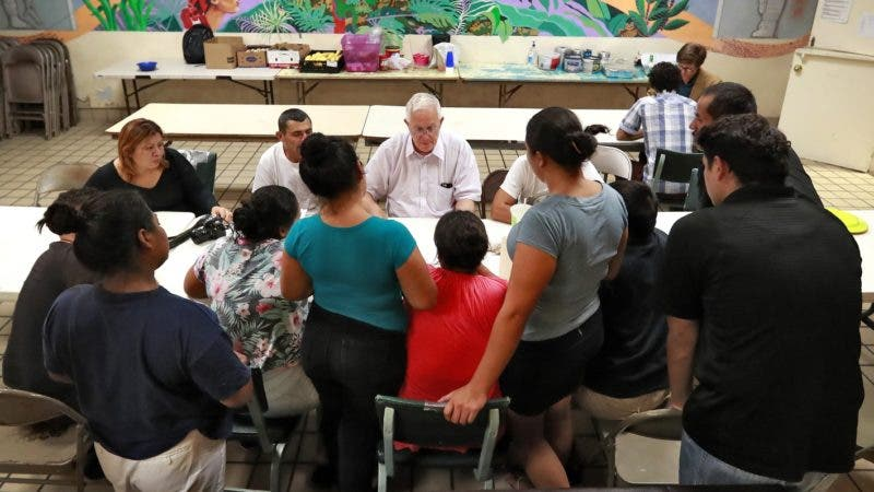 Ruben Garcia, director of the Annunciation House, speaks with migrant parents Tuesday, June 26, 2018, in El Paso, Texas. The migrants are some of the 32 parents separated from their children that are staying at the home as they wait to be reunited with their children. If the Trump administration has any hope of complying with a judge's order to reunite thousands of migrant children and parents within 30 days, it's going to have to clear away the red tape and confusion many immigrants have encountered so far. (AP Photo/Matt York)