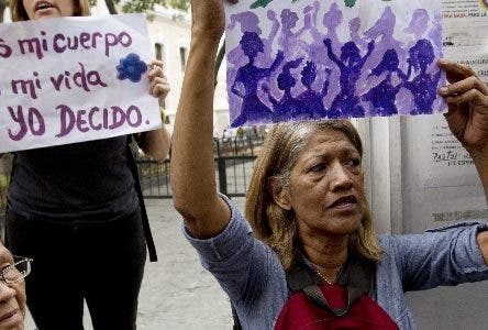 """Women shout slogans calling for a law that makes abortions legal, as one of them holds a sign that reads in Spanish """"Clandestine no more, legal abortion"""" during a protest outside Venezuela's Constitutional Assembly in Caracas, Venezuela, Wednesday, June 20, 2018. About 50 persons shouted slogans demanding for the legalization of abortion in Venezuela. (AP Photo/Fernando Llano)"""