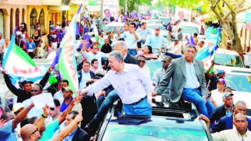 El expresidente Leonel Fernández saluda a los simpatizantes peledeístas durante su recorrido de ayer