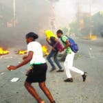 People run past a barricade during a protest over the cost of fuel in Port-au-Prince, Haiti, Friday, July 6, 2018. Major protests erupted Friday in Haiti as the government announced a sharp increase in gasoline prices, with demonstrators using burning tires and barricades to block major streets across the capital and in the northern city of Cap-Haitien. ( AP Photo/Dieu Nalio Chery)