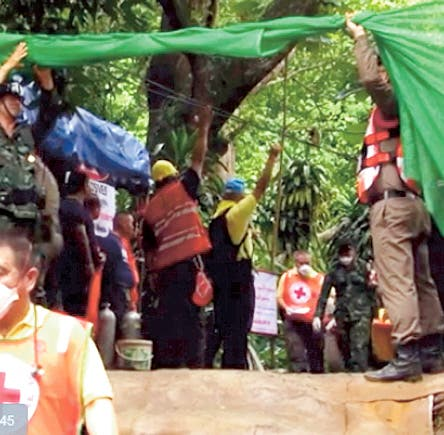 In this grab taken from video provide by Chiang Rai Public Relations Office, emergency workers carry a stretcher with one of the rescued boy to be transported by ambulance to a hospital, in Mae Sai, in the district of Chiang Rai, Thailand. Sunday, July 8, 2018. Expert divers Sunday rescued four of 12 boys from a flooded cave in northern Thailand where they were trapped with their soccer coach for more than two weeks, as a dangerous and complicated plan unfolded amid heavy rain and the threat of rising water underground. (Chiang Rai Public Relations Office via AP)
