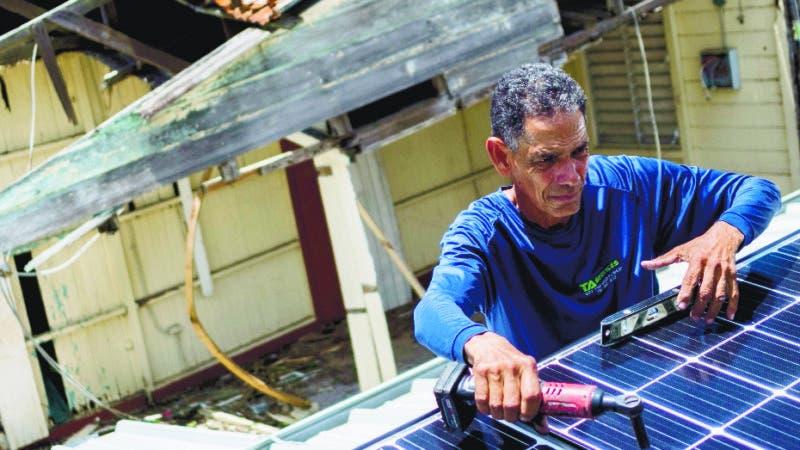 En esta imagen, tomda el 24 de julio de 2018, Julio Rosario instala un sistema de energía solar en su casa en Adjuntas, Puerto Rico. La ONG medioambiental Casa Pueblo instaló sistemas solares en dos ferreterías, una barbería y varias tiendas más pequeñas. Los activistas esperan que sirvan como un oasis de electricidad donde la gente pueda cargar sus celulares o almacenar sus medicamentos si fuese necesario durante una tormenta. (AP Foto/ Dennis M. Rivera Pichardo)