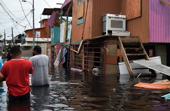 People walk in a flooded street next to damaged houses in Juana Matos, Catano, Puerto Rico, on September 21, 2017, after Hurricane Maria slammed into the region leaving a deadly trail of destruction. Puerto Rico was facing dangerous flooding and an island-wide power outage on Thursday following Hurricane Maria as the death toll from the powerful storm topped 15 in the tiny Caribbean island of Dominica.  / AFP / HECTOR RETAMAL