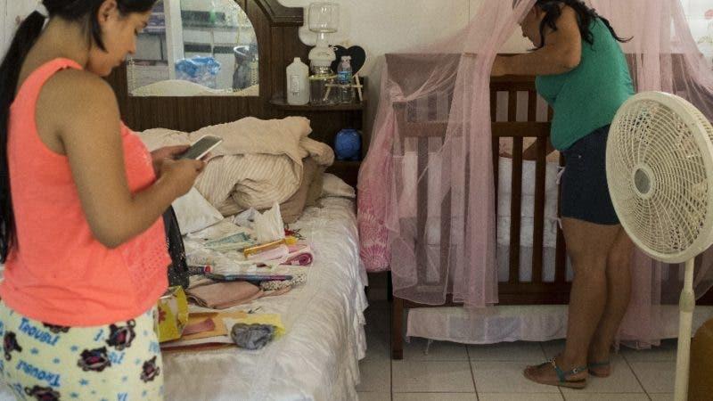 En esta imagen, tomada el 12 de julio de 2018, Joselyn Torres, de 17 años (derecha) mira a su hijo recién nacido en su casa, sin electricidad desde el paso de los huracanes Irma y María, en Adjuntas, Puerto Rico. Torres y su esposo, Steven Vilella, de 20 años, esperan el regreso de la electricidad aunque como muchos otros temen que este regreso a la normalidad pueda ser breve. (AP Foto/Dennis M. Rivera Pichardo)